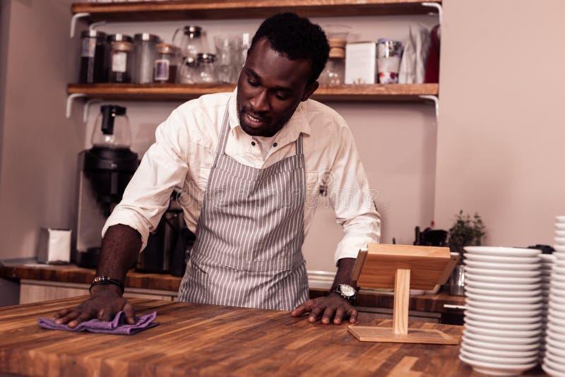 Positiv afro amerikansk man som använder en dammtrasa arkivfoton