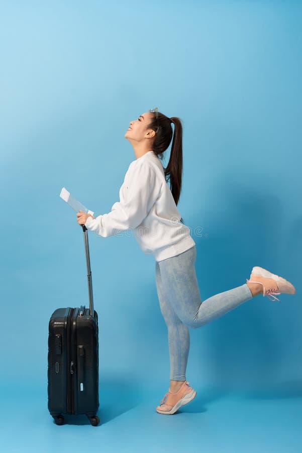 Positiv asiatisk kvinnlig som föreställas som isoleras på bakgrund med resväskan och biljetter för den plana dansen med glädje av arkivfoton