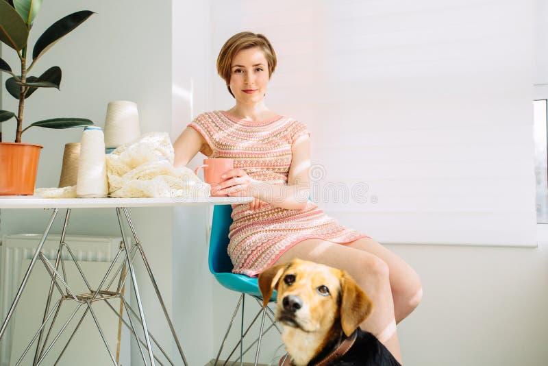 Positiv avkopplad kvinna som har avbrottet med kaffekoppen i hemmastadd inre för hemtrevlig arbetsplats Lycklig kvinnlig med henn arkivfoton