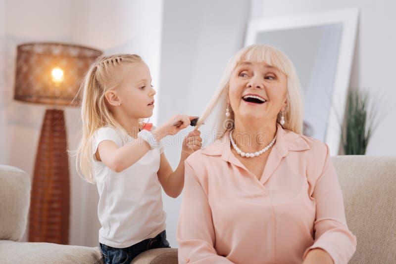 Positiv blond flicka som borstar hennes farmorhår arkivfoto