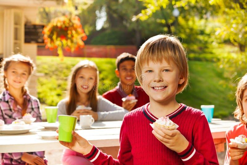 Positiv blond pojke med hans sitta för vänner arkivbild