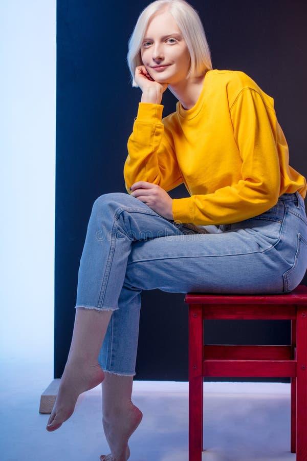 Positiv charmig blond kvinna som sitter på en stol arkivfoton