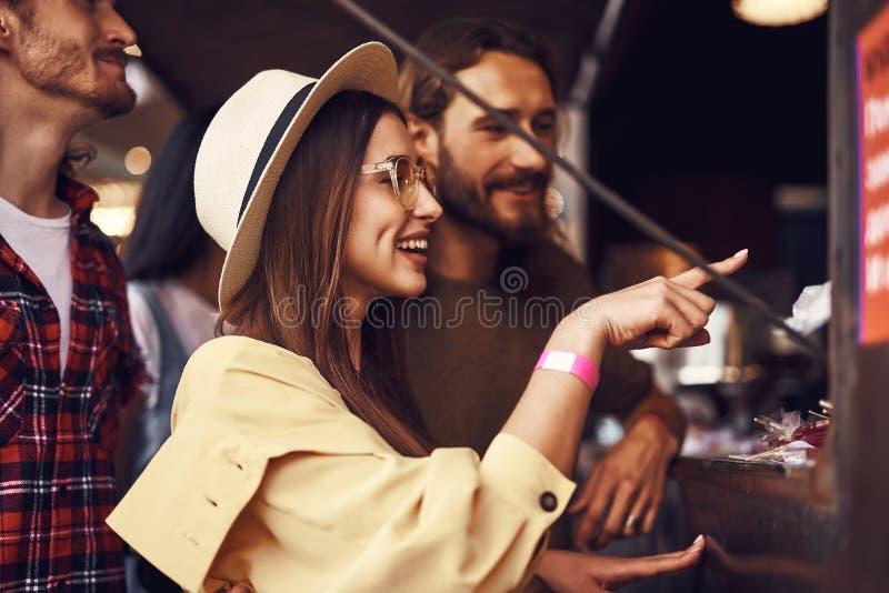 Positiv dam som ler och pekar till maten på foodcourt royaltyfri bild