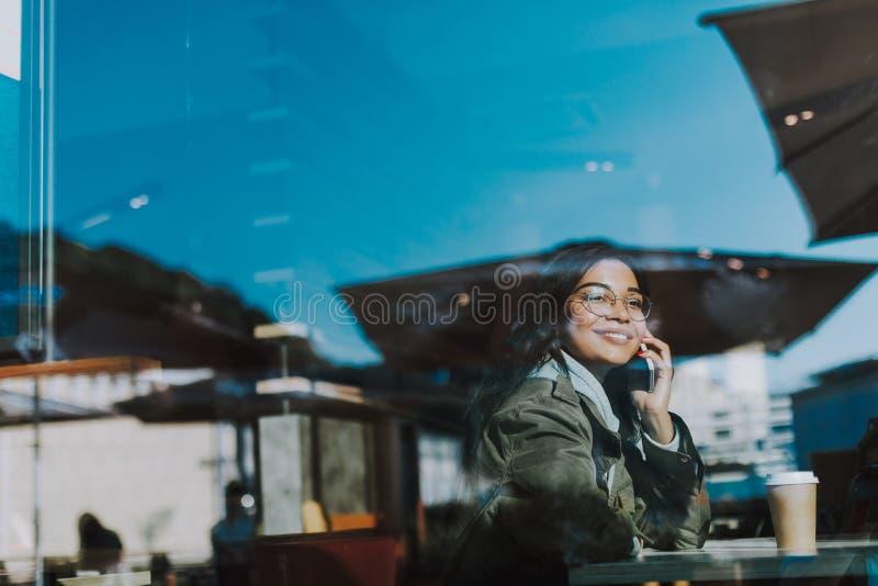 Positiv dam som talar på telefonen, medan sitta i kafét arkivfoto