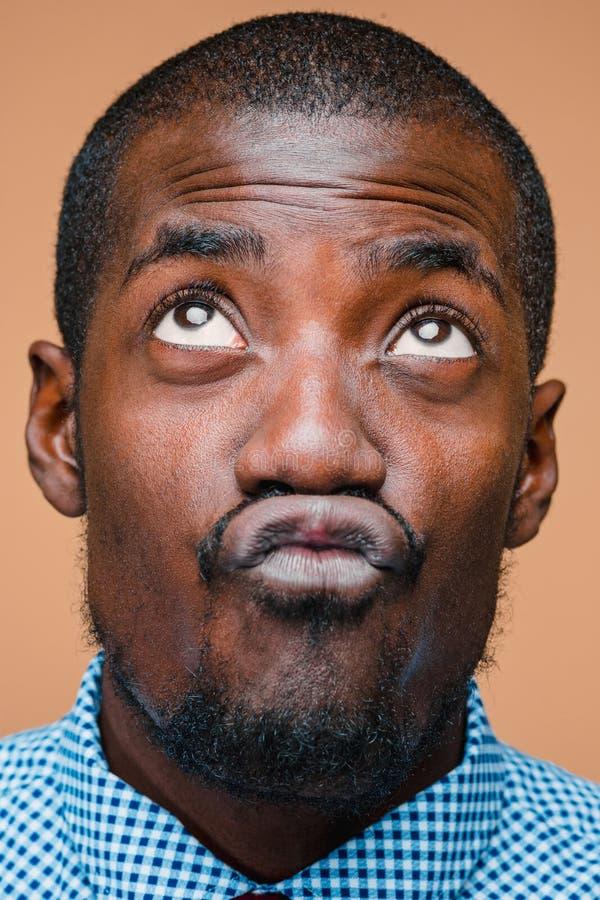 Positiv, das afro-amerikanischen Mann auf braunem Hintergrund denkt lizenzfreie stockfotografie