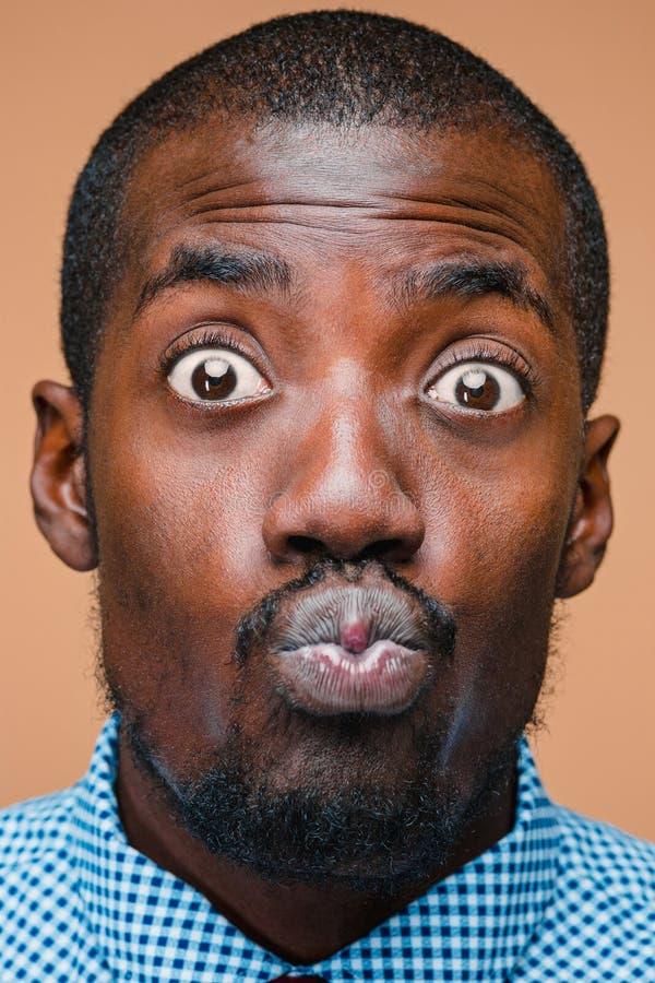 Positiv, das afro-amerikanischen Mann auf braunem Hintergrund denkt stockfotografie