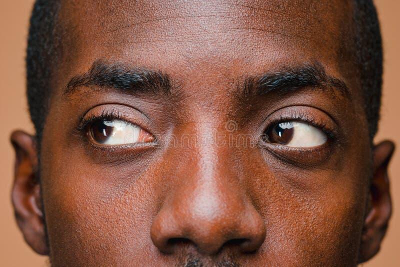 Positiv, das afro-amerikanischen Mann auf braunem Hintergrund denkt lizenzfreies stockbild