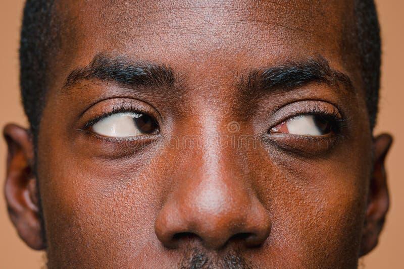 Positiv, das afro-amerikanischen Mann auf braunem Hintergrund denkt lizenzfreie stockfotos