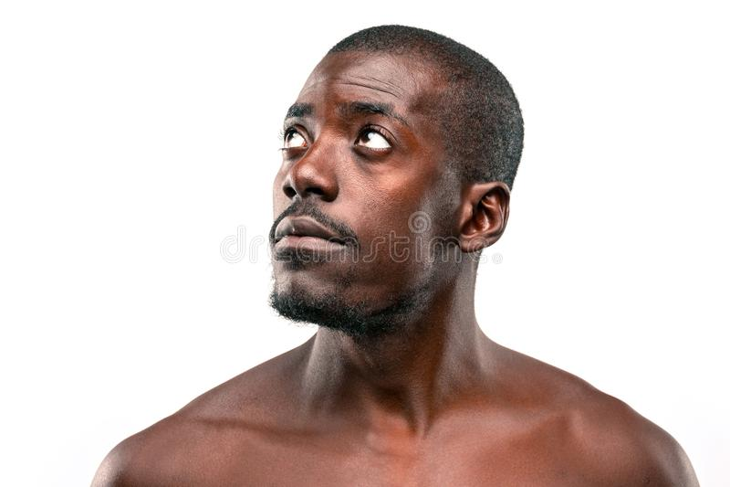 Positiv, das afro-amerikanischen Mann auf braunem Hintergrund denkt stockfoto