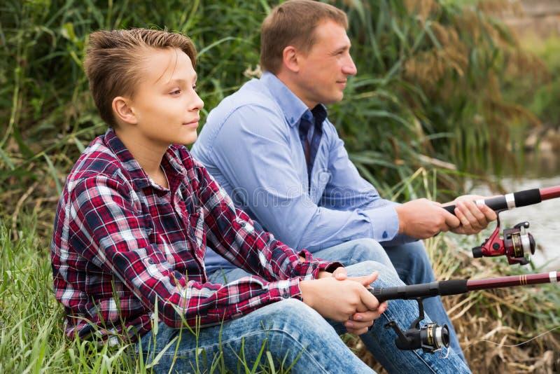 Positiv familj som tillsammans fiskar på den sötvattens- floden arkivfoton
