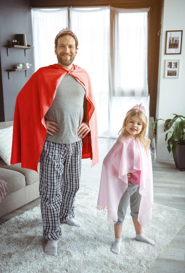 Positiv farsa och barn som har gyckel i lägenhet arkivfoton