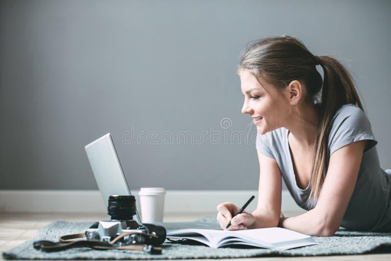 Positiv flicka med bärbara datorn som surfar internet som lägger på golvet royaltyfria foton