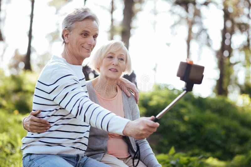 Positiv gealterte Paare, die draußen selfie nehmen stockfoto