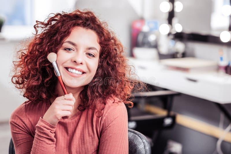 Positiv glad kvinna som tycker om hennes jobb i skönhetsfären royaltyfria bilder