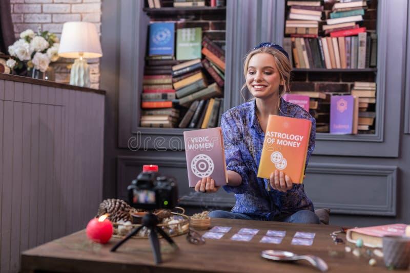 Positiv glad ung kvinna som rymmer två böcker arkivbilder