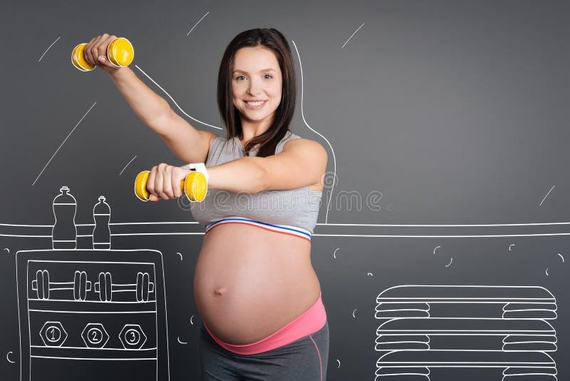 Positiv gravid kvinna som tycker om sportövningar arkivbild