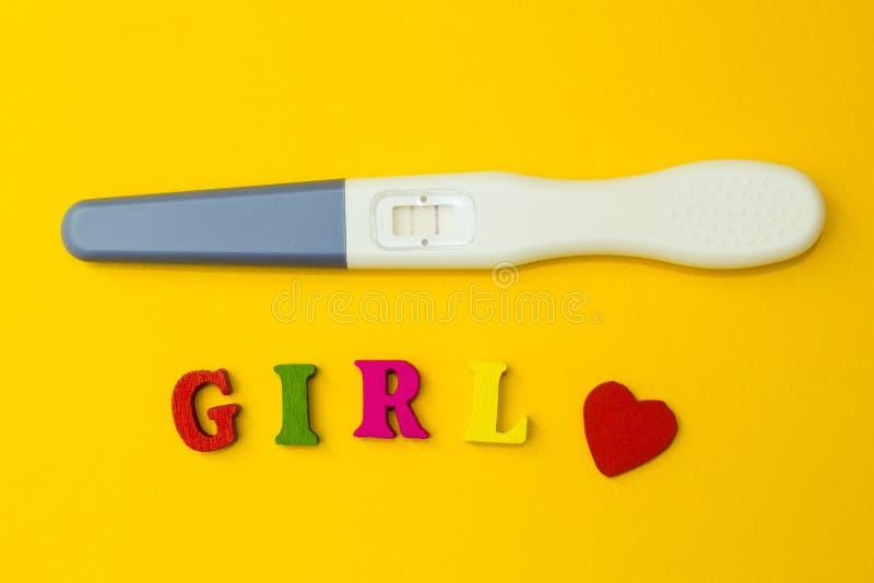 Positiv graviditetstest med två remsor och ordet 'flicka 'på en gul bakgrund royaltyfria bilder
