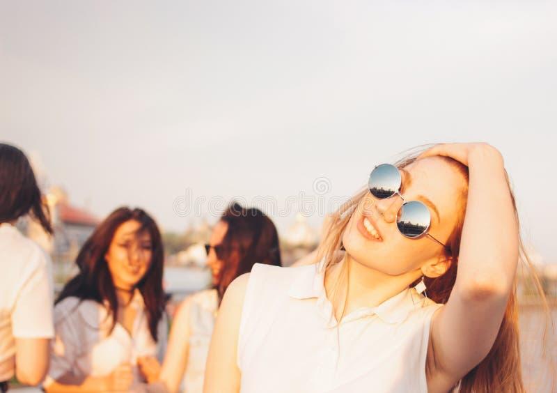 Positiv härlig lycklig röd haired flicka i spegelsolglasögon med vänner på bakgrund för blå himmel, sommarsolnedgångtid royaltyfria foton