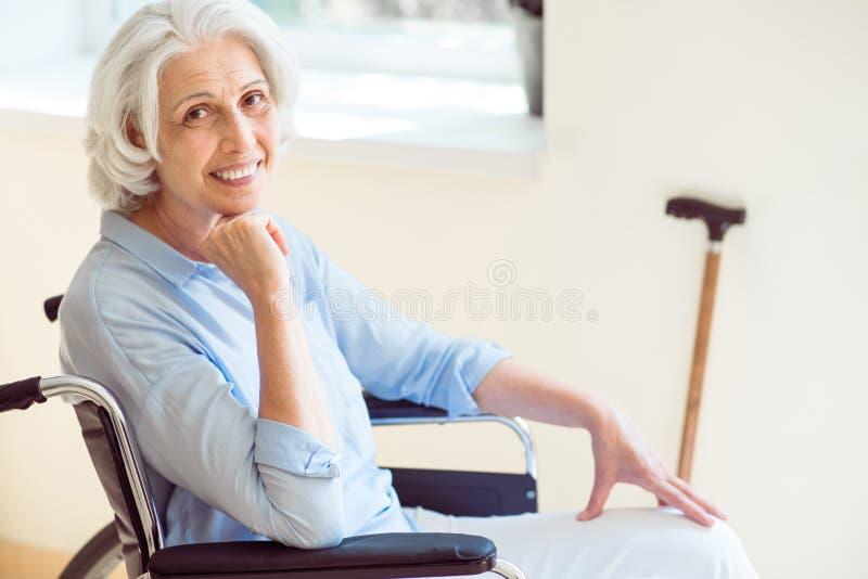 Positiv hög kvinna i rullstol royaltyfri bild