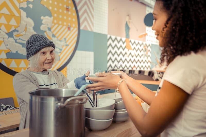 Positiv hög kvinna som tar hennes varma soppa royaltyfria foton