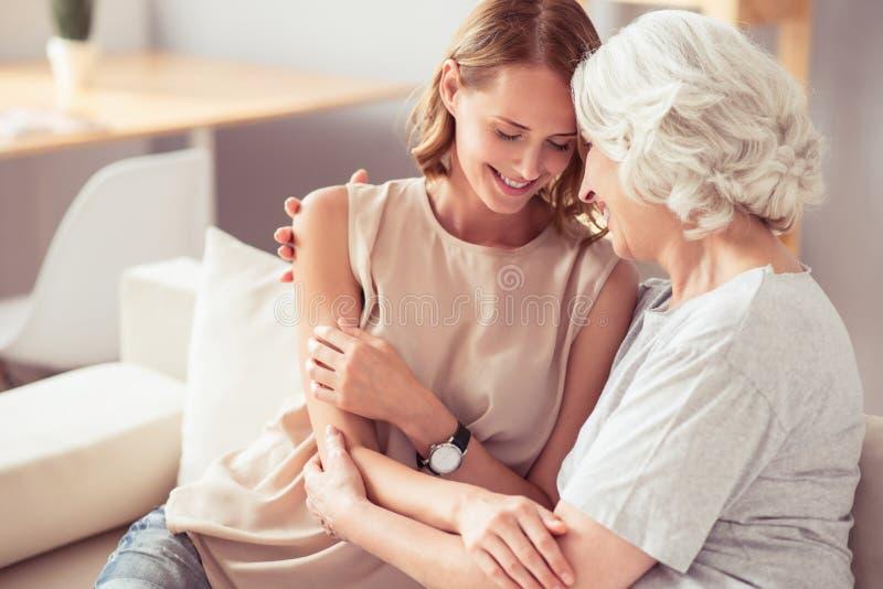 Positiv hög moder och hennes omfamna för dotter royaltyfria foton