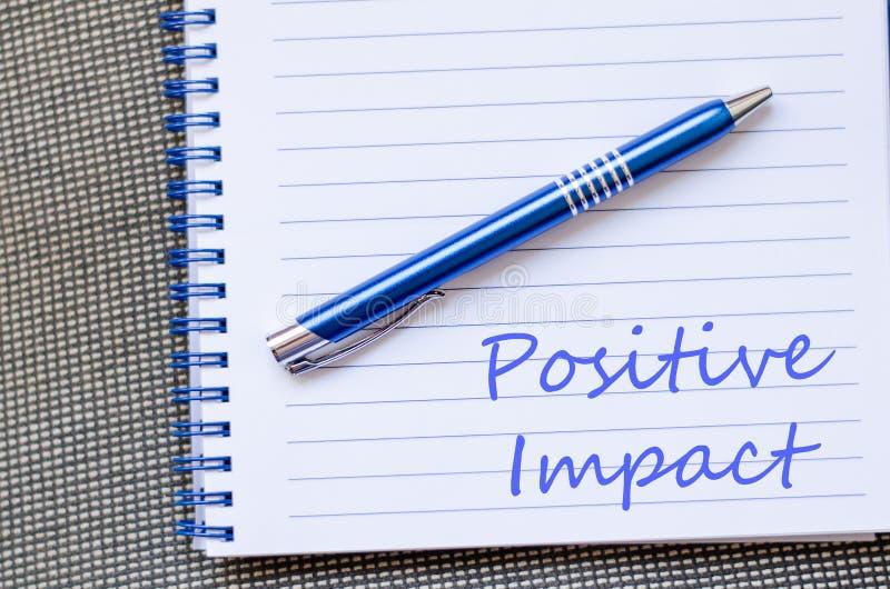 Positiv inverkan skriver på anteckningsboken royaltyfri bild