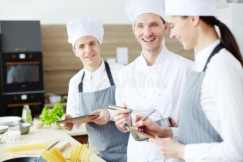 Positiv kock som tycker om att laga mat med unga anställda arkivfoto