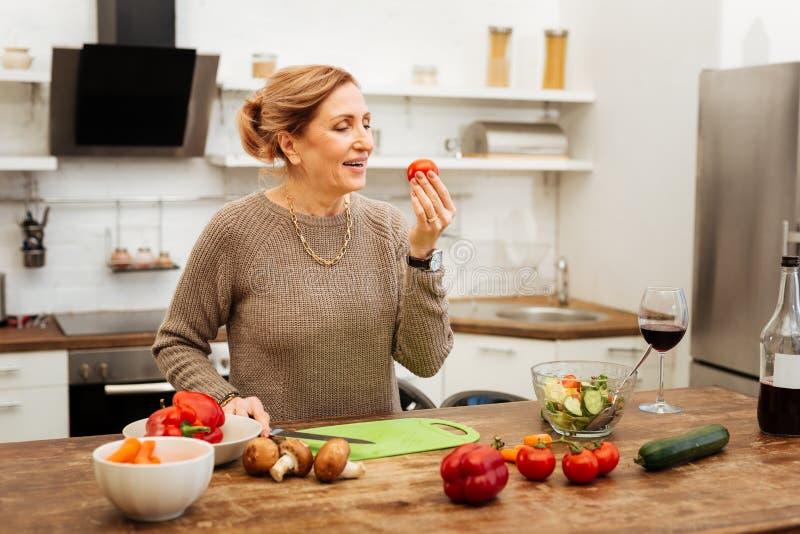 Positiv kvinna med bundet hår observera tomaten i hennes hand royaltyfri foto