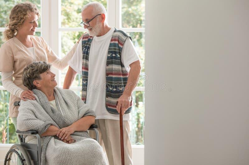 Positiv kvinna på rullstolen med att att bry sig sjuksköterskan och den äldre vännen med den gå pinnen royaltyfria foton