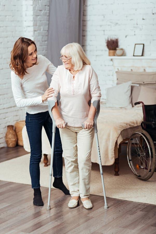 Positiv kvinnaportion honom farmor som går med kryckor arkivbild