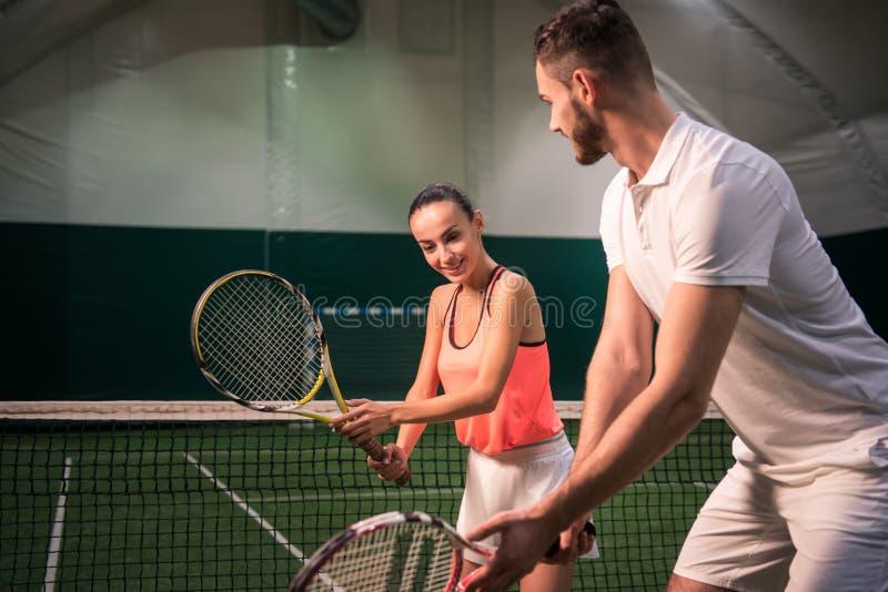 Positiv kvinnautbildning med tennisinstruktören arkivbild