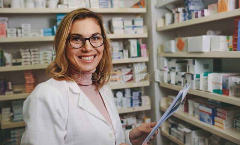 Positiv kvinnlig apotekare som arbetar i apotek arkivbilder