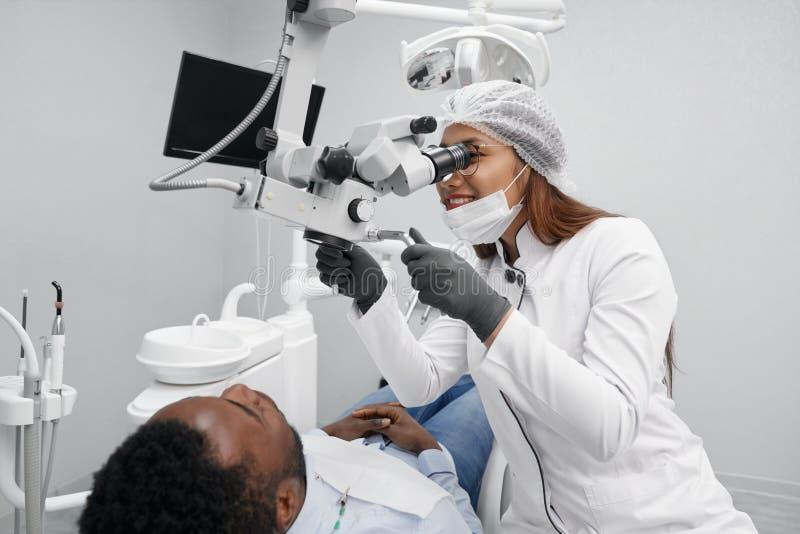Positiv kvinnlig tandläkare som kurerar tänder av den manliga patienten arkivbilder