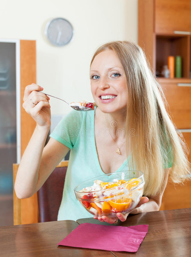 Positiv långhårig blond flicka som äter fruktsallad fotografering för bildbyråer