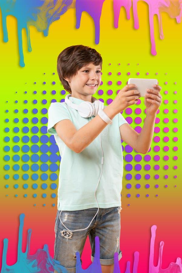 Positiv lockande pojke som nallar fotoet på bakgrund royaltyfri foto