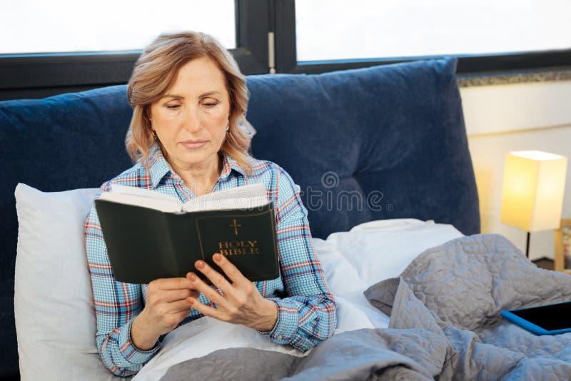 Positiv lugna kvinna som rymmer den öppna bibeln och läser hänsynsfullt arkivbilder