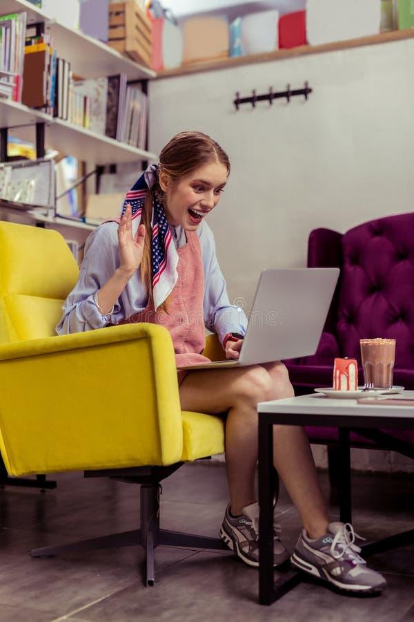 Positiv lycklig flicka som har den videopd appellen på hennes bärbar dator royaltyfria foton