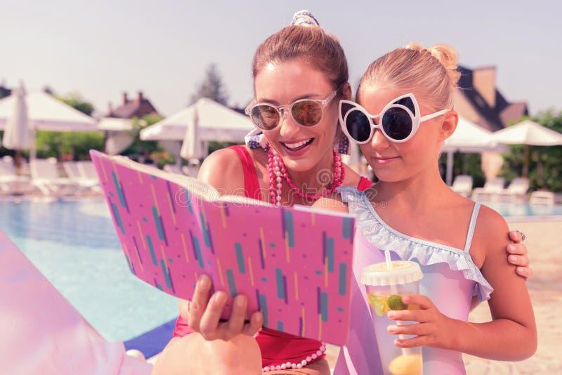 Positiv lycklig kvinna som läser en bok till hennes dotter arkivfoton