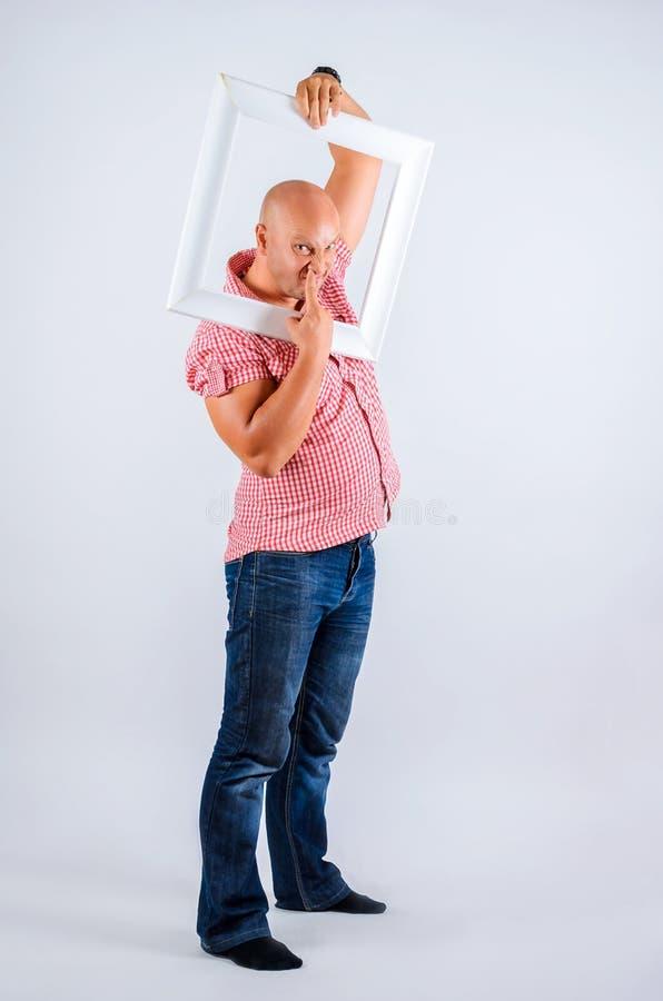Positiv man på en vit bakgrund med en ram från bilden, sinnesrörelser på hans framsida, bra lynne arkivbilder