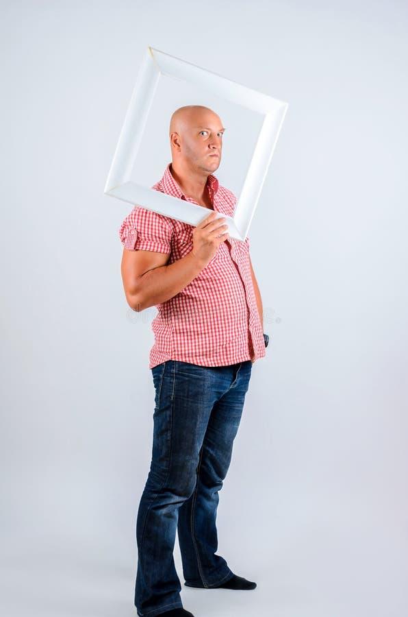 Positiv man på en vit bakgrund med en ram från bilden, sinnesrörelser på hans framsida, bra lynne royaltyfri foto