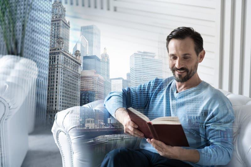 Positiv man som hemma läser en bok arkivfoton