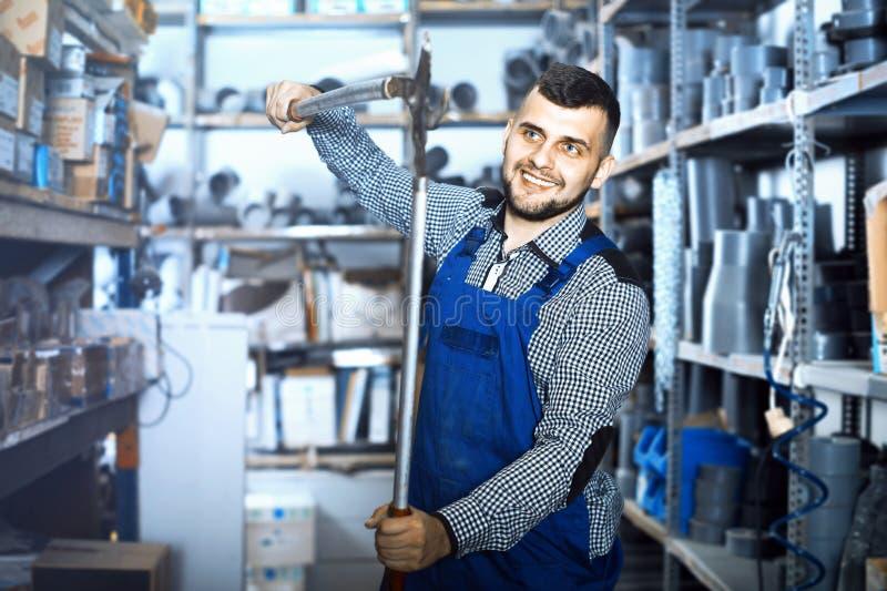 Positiv manlig arbetare som visar olika hjälpmedel arkivfoton