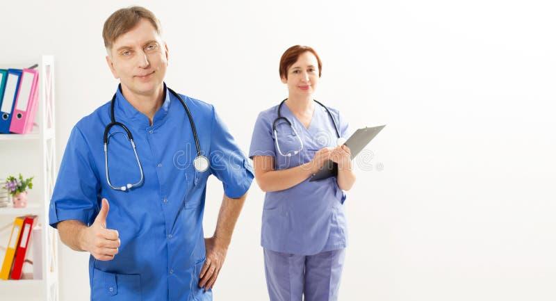 Positiv manlig doktorsshow som tecken och kvinnlig doktor med mappen i det medicinska kontoret, medicinsk försäkring, kopieringsu arkivbilder