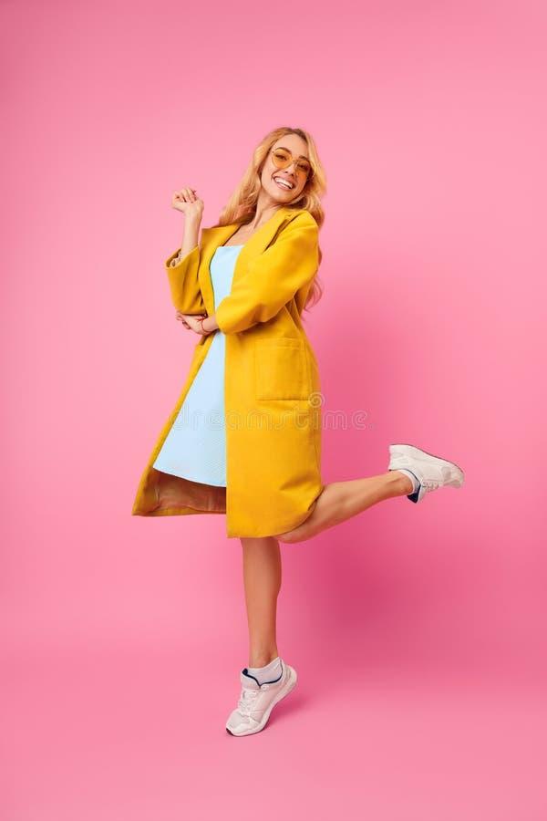 Positiv Millennial flickabanhoppning och posera på rosa bakgrund arkivfoton