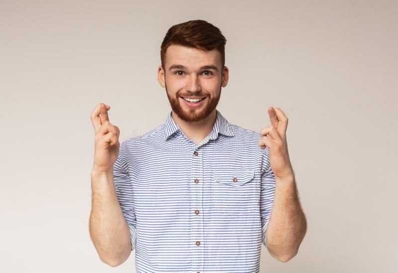 Positiv millennial grabb som korsar fingrar och gör önska royaltyfria foton