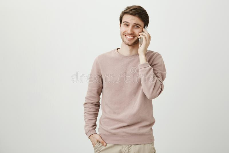 Positiv och stilig ung caucasian man med borstet som ler, medan tala på smartphonen som står med handen i fack arkivfoto