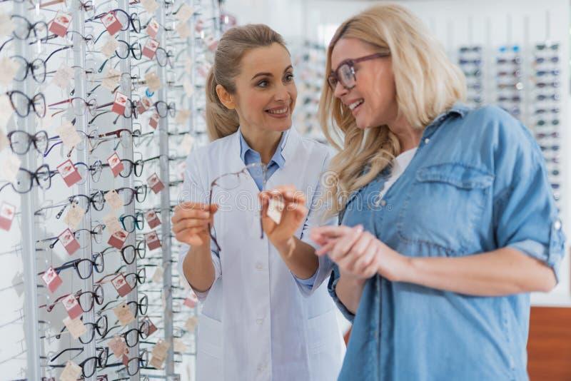 Positiv optiker som hjälper hennes patient att välja exponeringsglas arkivbild