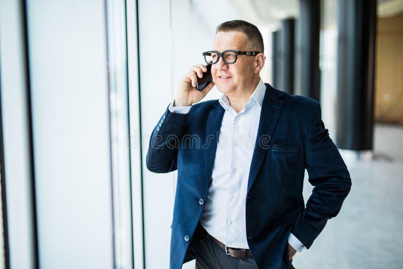 Positiv säker lyckad hög affärsman i formellt dräktanseende på fönstret och beskådacityscape, medan tala på mo royaltyfria bilder