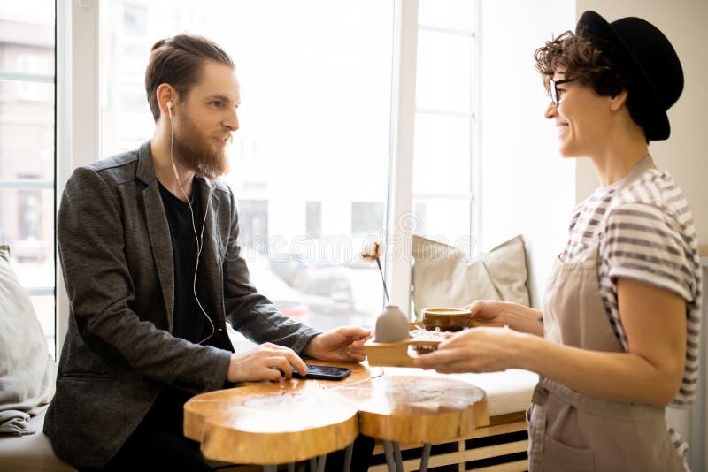 Positiv servitris som ger magasinet med kaffe till kunden royaltyfri foto