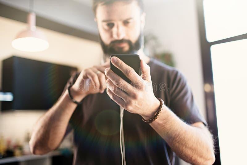 Positiv skäggig grabb som bär tillfällig grå t-skjorta lyssnande musik i hörlurar som kontrollerar sociala nätverk på smar arkivfoton